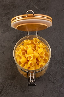 Een gele ruwe binnenkantkom van vooraanzicht italiaanse droge deegwaren die op dark wordt geïsoleerd