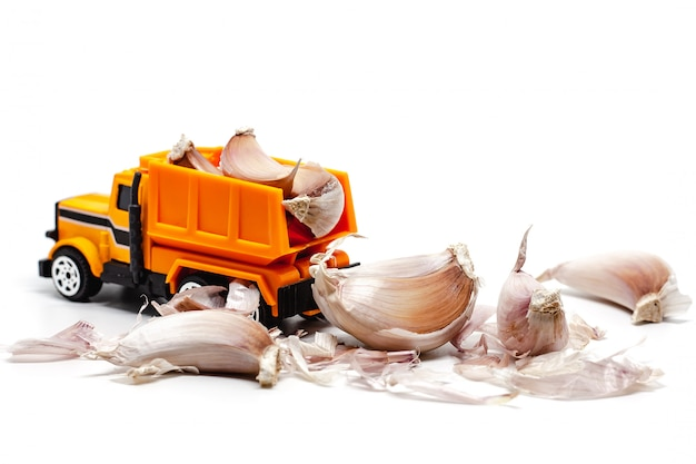 Een gele stuk speelgoed stortplaatsvrachtwagen met knoflook op witte achtergrond