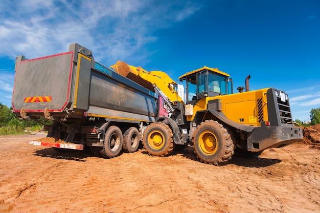 Een gele tractor laadt grond in een dumptruck