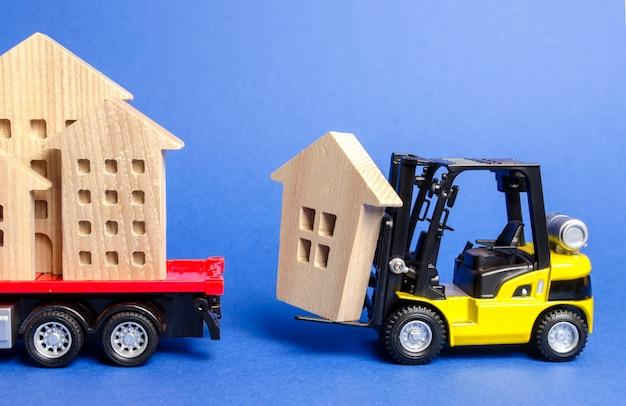 Een gele vorkheftruck laadt een houten figuur van een huis in een vrachtwagen.