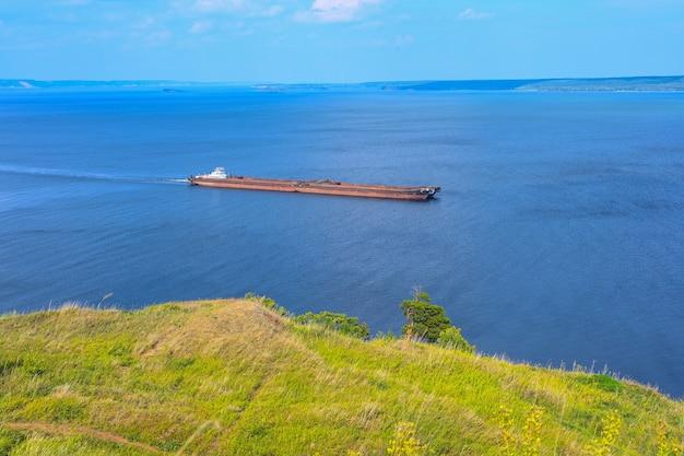 Een gelede sleepboot en barge bulkcarrier vervoert zand en bouwmaterialen op de rivier. de grote schuit vaart langs de brede wolga. transport industrie.