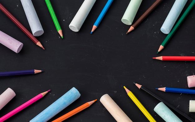 Een gelijkmatige laag kleurpotloden wordt op een zwarte kindertekentafel gelegd met een kopie van de ruimte.
