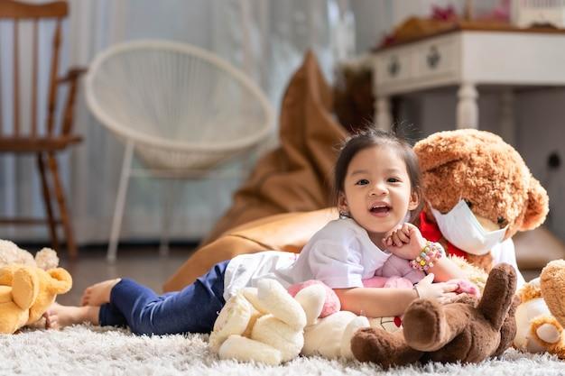 Een gelukkig aziatisch meisje dat en op de vloer glimlacht ligt met het spelen van teddybeer