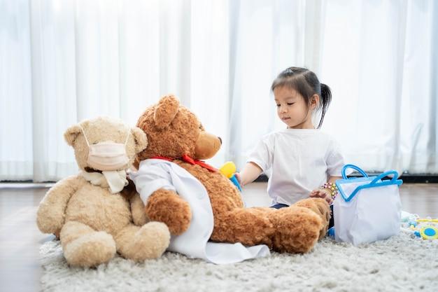 Een gelukkig aziatisch meisje speelt teddybeer