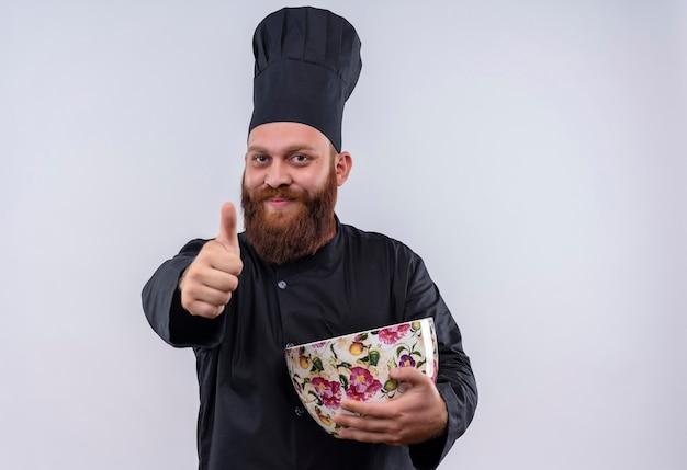 Een gelukkig bebaarde chef-kok man in zwart uniform met enorme kop en duimen opdagen terwijl hij naar de camera op een witte muur kijkt