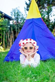 Een gelukkig en vrolijk kind een meisje ligt op het groene gras bij de tipi op de speelplaats in een zonnebril in de zomer en glimlacht