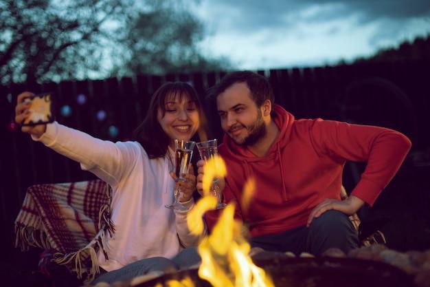 Een gelukkig getrouwd stel zit bij het vuur en neemt een selfie aan de telefoon