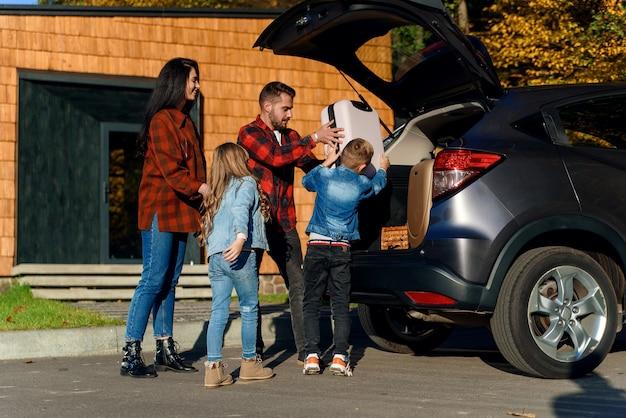 Een gelukkig gezin laadt bagage in de kofferbak van een auto als ze op vakantie gaan met het gezin.