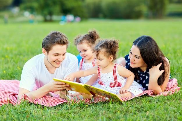 Een gelukkig gezin leest een boek in het park.