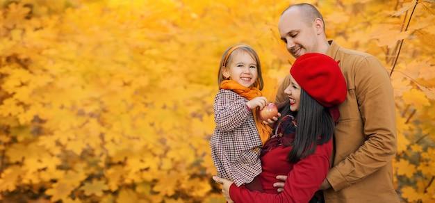Een gelukkig gezin met een dochter in hun armen tegen de achtergrond van herfstgebladerte van esdoorn