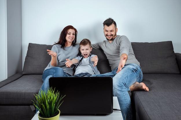 Een gelukkig gezin met een glimlach die iets in een laptop bekijkt