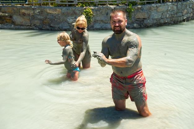 Een gelukkig gezin neemt een modderbad in een resort in turkije. familiewelzijn in therapeutische modder