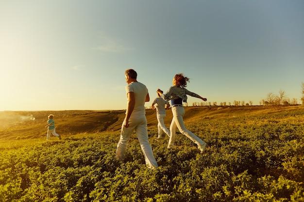 Een gelukkig gezin rent over het veld bij zonsondergang in de zon.
