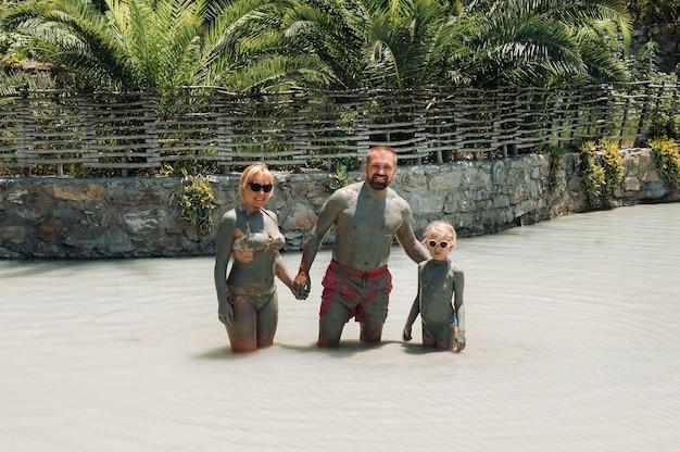 Een gelukkig gezin van drie neemt modderbaden in een resort in turkije.familie wellness in therapeutische modder.turkije.
