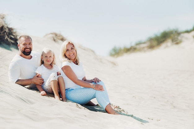 Een gelukkig gezin van drie op de zandduinen van de oostzee nabij de stad nida
