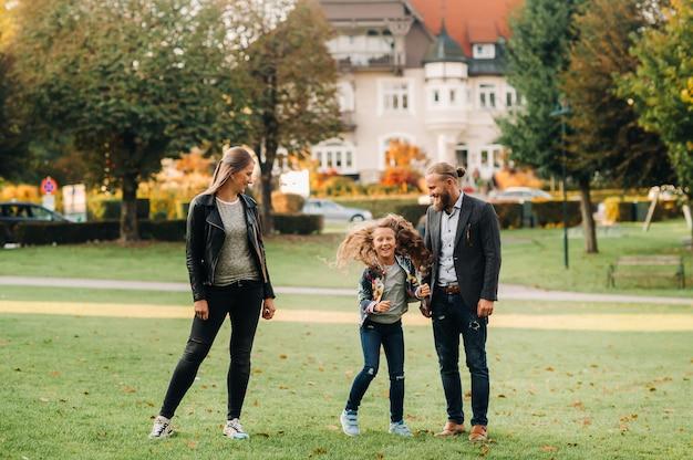 Een gelukkig gezin van drie rent door het gras in de oude binnenstad van oostenrijk, een gezin loopt door een klein stadje in oostenrijk, europa, velden am werten zee.