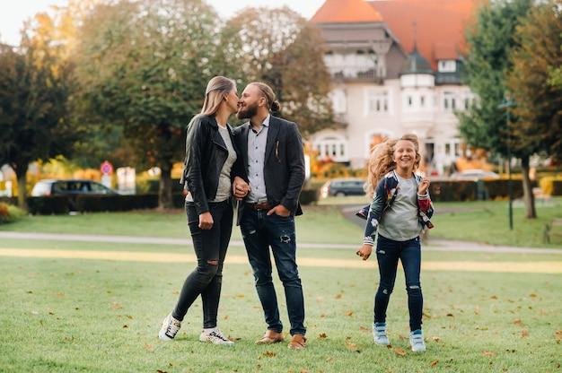 Een gelukkig gezin van drie rent door het gras in de oude binnenstad van oostenrijk