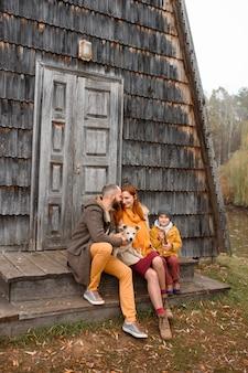 Een gelukkig gezin zit op de trap voor de ingang van het huis.