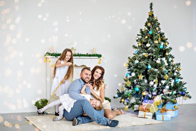 Een gelukkig gezin zit op het tapijt bij de witte open haard met een elegante kerstboom