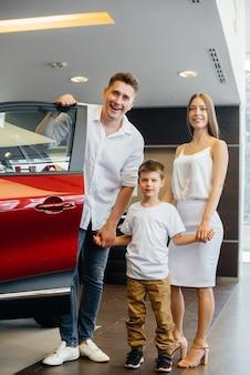 Een gelukkig jong gezin kiest en koopt een nieuwe auto bij een autodealer. een nieuwe auto kopen.
