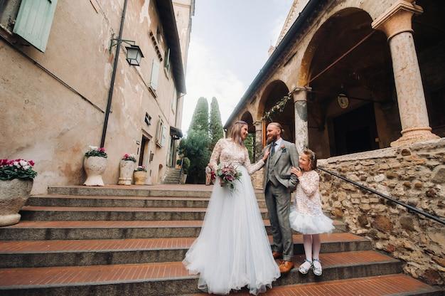 Een gelukkig jong gezin loopt door het oude centrum van sirmione in italië