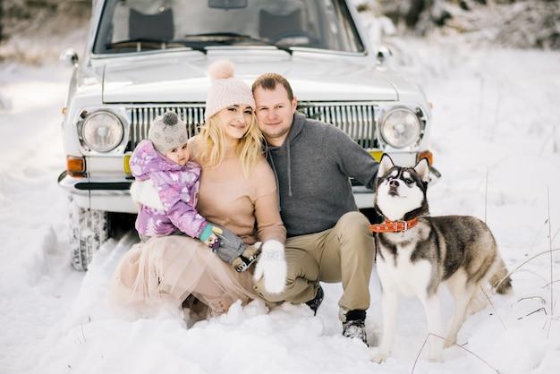 Een gelukkig jong gezin met een klein kind bereidt zich voor op kerstmis, wandelen met een husky hond op de achtergrond van een retro auto, op het dak van een kerstboom en geschenken in de winter besneeuwde bos.