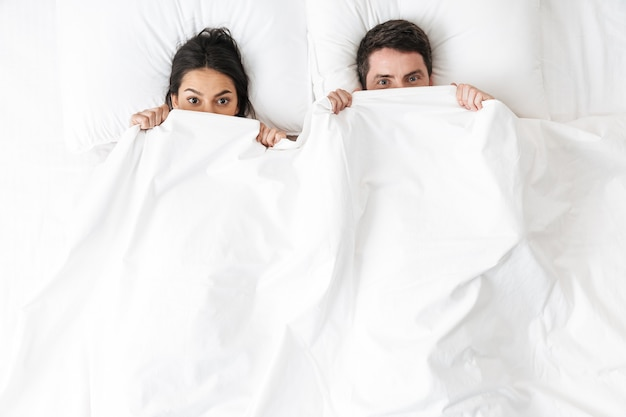 Een gelukkig jong liefdevol stel ligt in bed en verbergt zich onder de deken