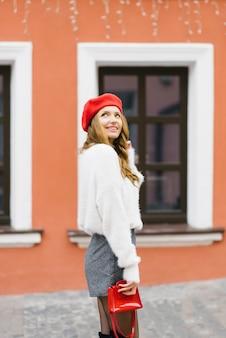 Een gelukkig jong meisje in een rode baret en met een rode kleine tas kijkt omhoog naar de lucht en glimlacht