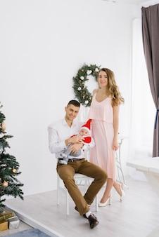 Een gelukkig jong mooi gezin met een jonge zoon in een kerstmankostuum houdt hem in hun armen in de woonkamer ingericht voor kerstmis