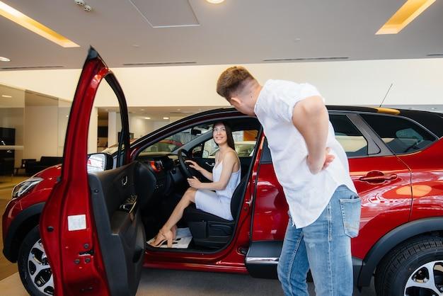 Een gelukkig jong stel kiest en koopt een nieuwe auto bij een autodealer. een nieuwe auto kopen.