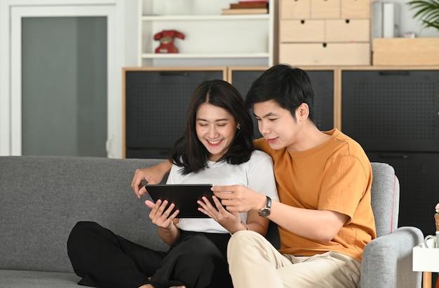 Een gelukkig jong stel ontspant en gebruikt tablet op bank thuis