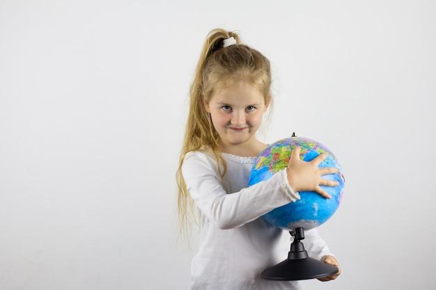 Een gelukkig kind houdt een wereldbol in zijn handen en verkent de landen waar hij heen wil. het concept van een wereld zonder grenzen