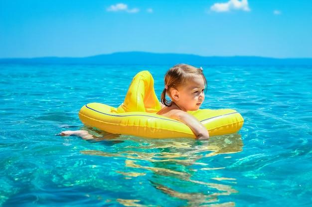 Een gelukkig kind in een vest aan het spelen op zee