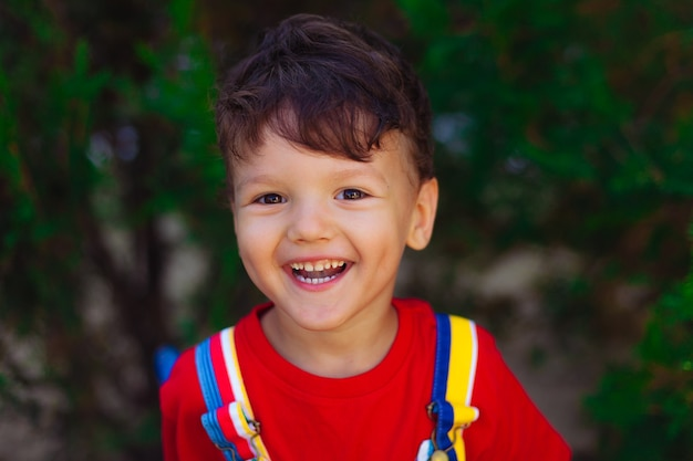 Een gelukkig kind kijkt in de camera helder en kleurrijk portret van een dappere jongen in een rode t-shirt op een...