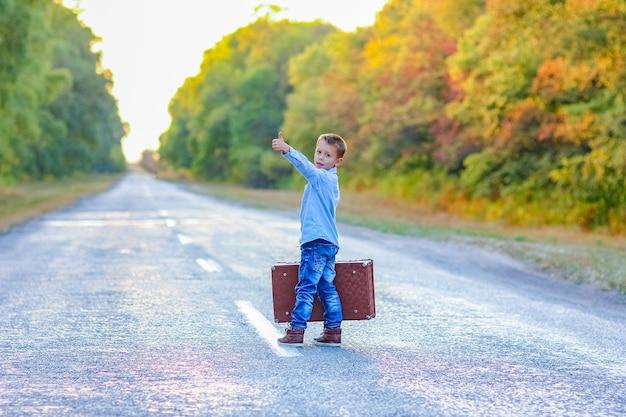 Een gelukkig kind met een koffer op de weg in het park reizen