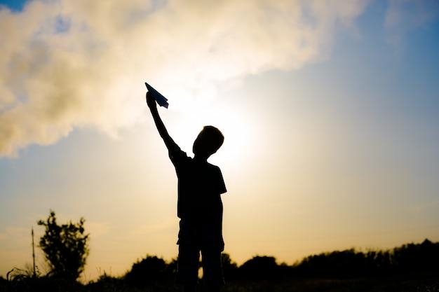 Een gelukkig kind speelt met een papieren vliegtuigje bij zonsondergang. lessen met kinderen buiten. levensstijl