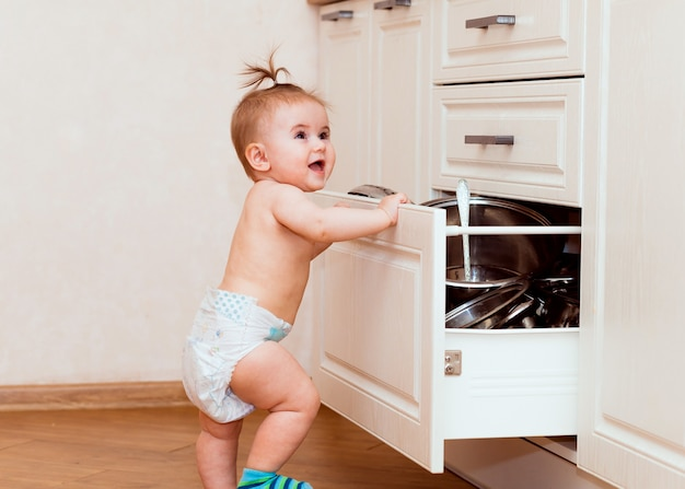 Een gelukkig kind staat in de buurt van een open kast in de keuken. kind in de witte keuken. kind lacht in een witte keuken.