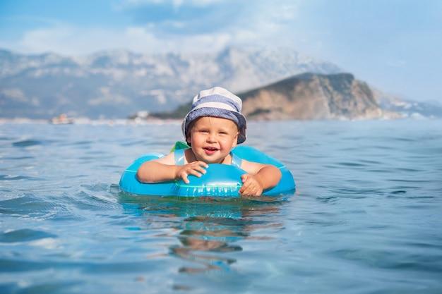 Een gelukkig kind zwemt in een zwemmende ring in de adriatische zee