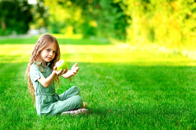 Een gelukkig kindmeisje in de zomer op het gazon met een groene appel zit op het gras en glimlacht