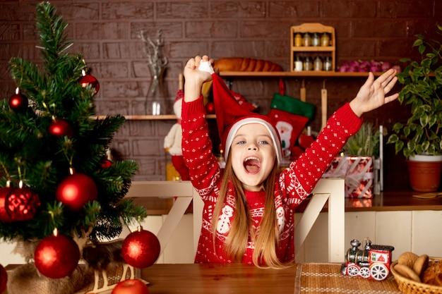 Een gelukkig kindmeisje in een kerstmuts in een donkere keuken bij de kerstboom met rode ballen verheugt zich en glimlacht, het concept van nieuwjaar en kerstmis