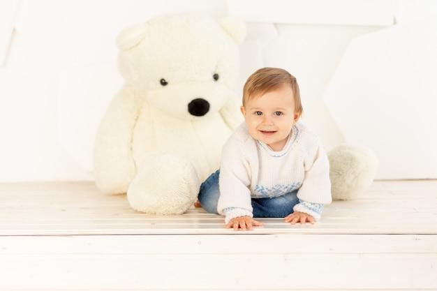 Een gelukkig klein kind van zes maanden oud in een gebreid warm jasje en een spijkerbroek kruipt thuis bij een grote teddybeer