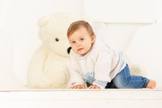 Een gelukkig klein kind van zes maanden oud in een gebreid warm jasje en spijkerbroek kruipt thuis in de buurt van een grote teddybeer