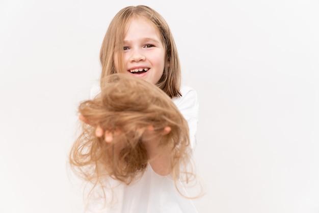 Een gelukkig klein meisje houdt in handen bijgesneden haar na het knippen op een witte achtergrond. betekent om voor het haar van kinderen te zorgen. schoonheidssalon voor kinderen.