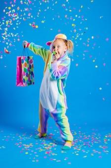 Een gelukkig klein meisje in een eenhoorn kigurumi heeft een cadeauzakje