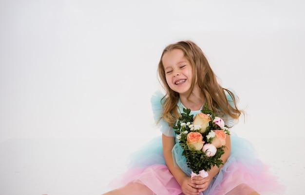 Een gelukkig klein meisje in een feestelijke jurk zit en houdt een boeket bloemen vast op een witte achtergrond met een kopie van de ruimte