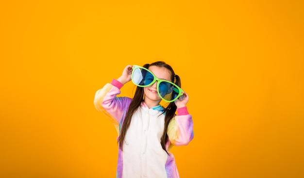 Een gelukkig klein meisje in een kigurumi-pyjama en een grote bril staat op een gele achtergrond met een kopie van de ruimte
