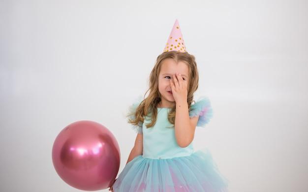 Een gelukkig klein meisje in een papieren pet en een nette jurk staat met een roze ballon op een witte achtergrond met een plek voor tekst
