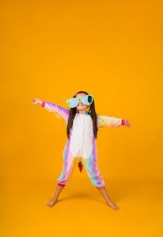 Een gelukkig klein meisje in een pluche pak en grote bril op een gele achtergrond met een plek voor tekst