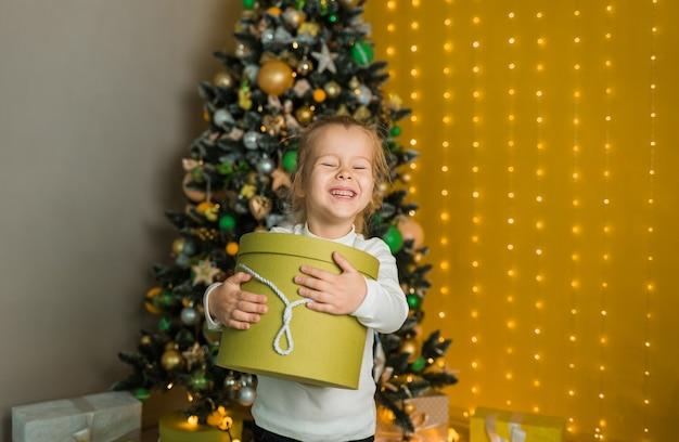 Een gelukkig klein meisje in een witte trui staat met een groen cadeau in de buurt van de kerstboom en sluit haar ogen