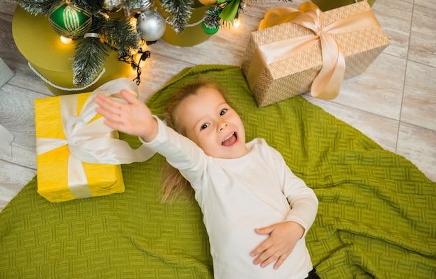 Een gelukkig klein meisje ligt op een groene gebreide deken onder een kerstboom met geschenken en strekt haar hand uit